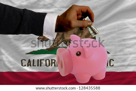 Man putting dollar into piggy rich bank flag of us state of california in foreign currency because of inflation - stock photo