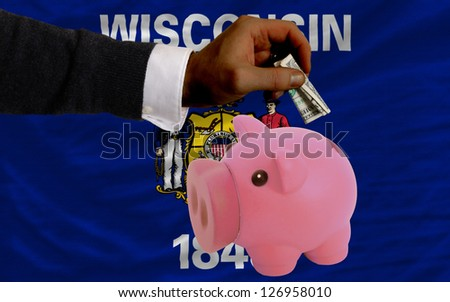 Man putting dollar into piggy rich bank flag of us state of wisconsin in foreign currency because of inflation - stock photo