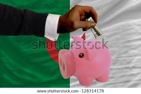 Man putting dollar into piggy rich bank national flag of algeria in foreign currency because of inflation - stock photo