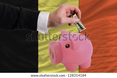 Man putting dollar into piggy rich bank national flag of belgium in foreign currency because of inflation - stock photo