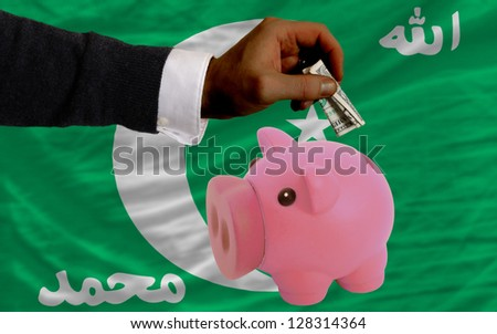 Man putting dollar into piggy rich bank national flag of  comoros in foreign currency because of inflation - stock photo