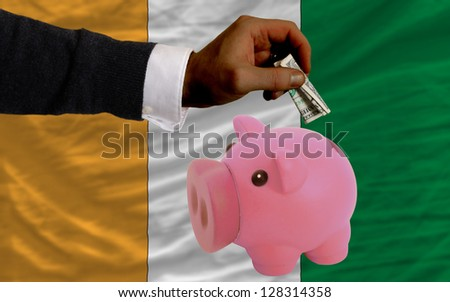 Man putting dollar into piggy rich bank national flag of cote ivore in foreign currency because of inflation - stock photo