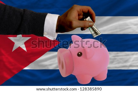 Man putting dollar into piggy rich bank national flag of cuba in foreign currency because of inflation - stock photo