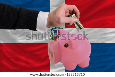Man putting dollar into piggy rich bank national flag of dominican in foreign currency because of inflation