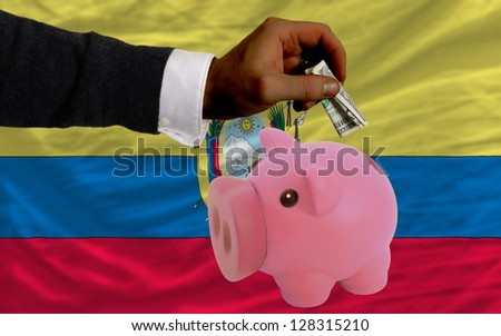 Man putting dollar into piggy rich bank national flag of ecuador in foreign currency because of inflation