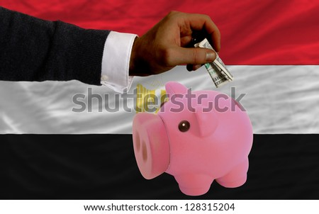 Man putting dollar into piggy rich bank national flag of egypt in foreign currency because of inflation - stock photo