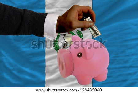 Man putting dollar into piggy rich bank national flag of guatemala in foreign currency because of inflation