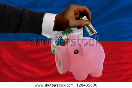 Man putting dollar into piggy rich bank national flag of haiti in foreign currency because of inflation - stock photo