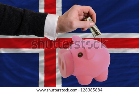 Man putting dollar into piggy rich bank national flag of iceland in foreign currency because of inflation