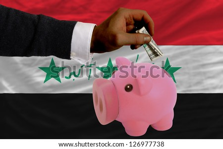 Man putting dollar into piggy rich bank national flag of iraq in foreign currency because of inflation - stock photo