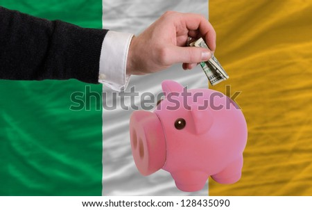 Man putting dollar into piggy rich bank national flag of ireland in foreign currency because of inflation - stock photo