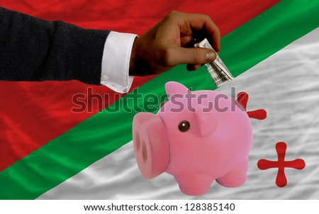 Man putting dollar into piggy rich bank national flag of  katanga in foreign currency because of inflation - stock photo