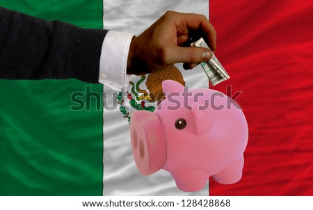 Man putting dollar into piggy rich bank national flag of mexico in foreign currency because of inflation - stock photo