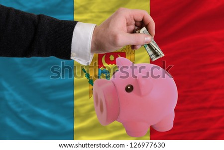 Man putting dollar into piggy rich bank national flag of moldova in foreign currency because of inflation