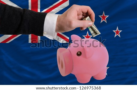 Man putting dollar into piggy rich bank national flag of new zealand in foreign currency because of inflation - stock photo