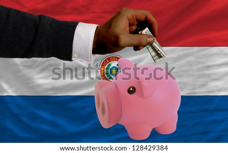 Man putting dollar into piggy rich bank national flag of paraguay in foreign currency because of inflation - stock photo