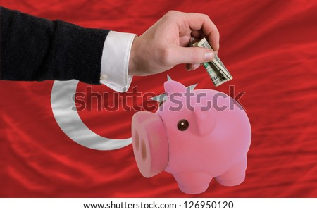 Man putting dollar into piggy rich bank national flag of turkey in foreign currency because of inflation - stock photo