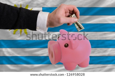 Man putting dollar into piggy rich bank national flag of uruguay in foreign currency because of inflation - stock photo