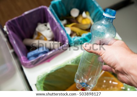 Man putting empty plastic bottle in recycling bin in the kitchen. Person in the house kitchen separating waste. Different trash can with colorful garbage bags. Top view