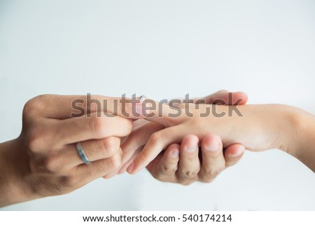 Man putting engagement ring on hand of woman