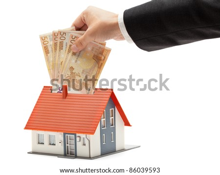 Man putting Euro banknotes into model house - real estate investment concept