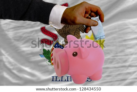 Man putting euro into piggy rich bank and flag of us state of illinois in foreign currency because of insecurity and inflation