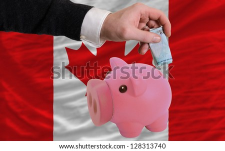Man putting euro into piggy rich bank and national flag of canada in foreign currency because of insecurity and inflation - stock photo