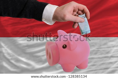 Man putting euro into piggy rich bank and national flag of indonesia in foreign currency because of insecurity and inflation - stock photo