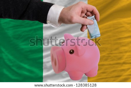 Man putting euro into piggy rich bank and national flag of ireland in foreign currency because of insecurity and inflation - stock photo