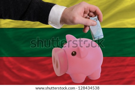 Man putting euro into piggy rich bank and national flag of lithuania in foreign currency because of insecurity and inflation - stock photo