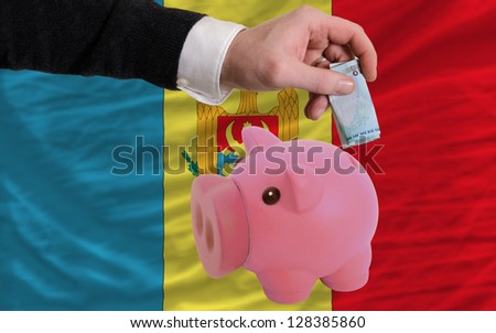Man putting euro into piggy rich bank and national flag of moldova in foreign currency because of insecurity and inflation - stock photo