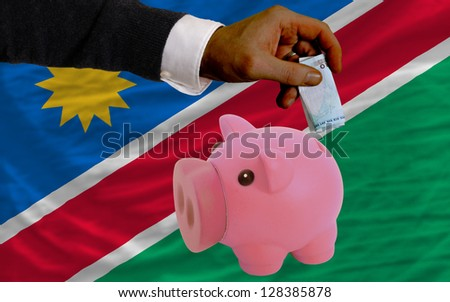 Man putting euro into piggy rich bank and national flag of namibia in foreign currency because of insecurity and inflation - stock photo