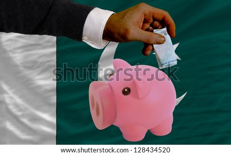 Man putting euro into piggy rich bank and national flag of pakistan in foreign currency because of insecurity and inflation - stock photo