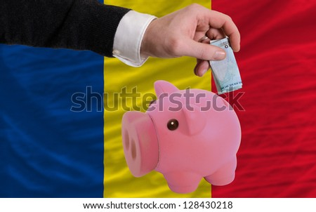 Man putting euro into piggy rich bank and national flag of romania in foreign currency because of insecurity and inflation - stock photo