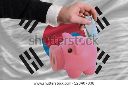 Man putting euro into piggy rich bank and national flag of south korea in foreign currency because of insecurity and inflation - stock photo