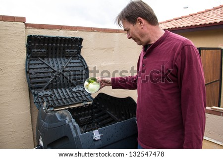man putting food scraps in compost bin - stock photo