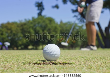 Man putting golf ball with hole  - stock photo