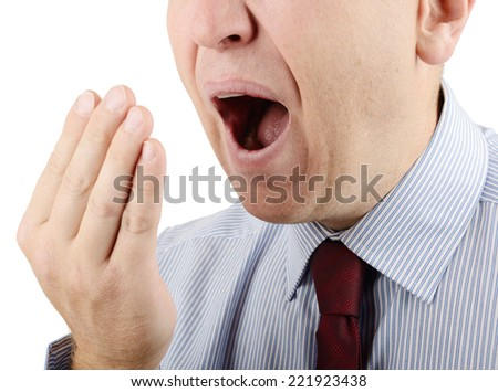 Man putting hand over mouth while yawning - stock photo