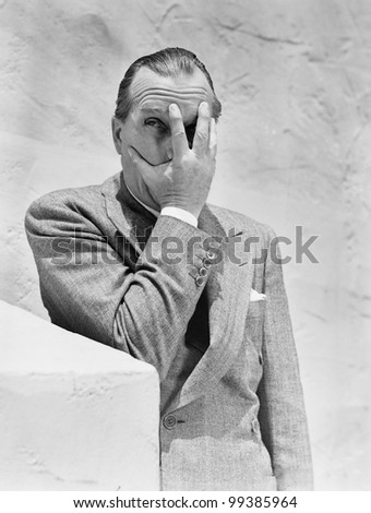 Man putting his hand in front of his face and peeking through his fingers - stock photo