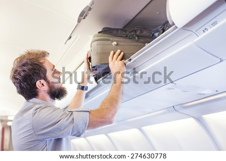 man putting luggage on the top shelf on airplane - stock photo
