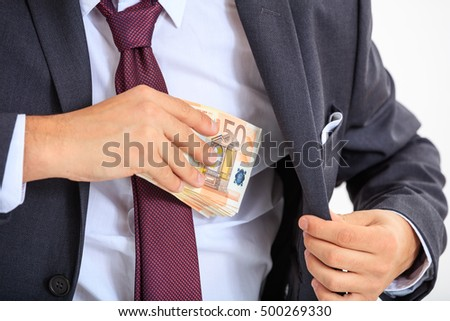 Man putting money in his suit
