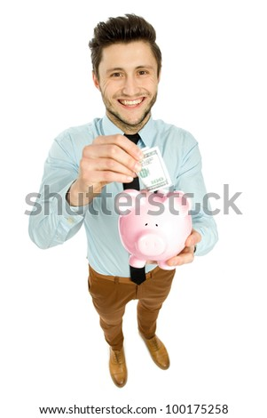 Man putting money in piggy bank - stock photo