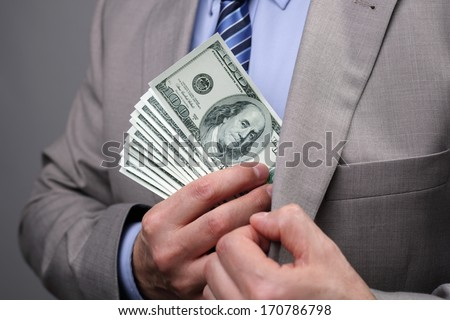 Man putting money in suit jacket pocket concept for corruption, bribing, paying or business wealth - stock photo