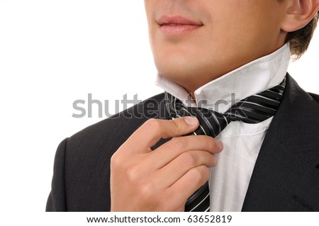 Man putting on necktie. Isolated on white