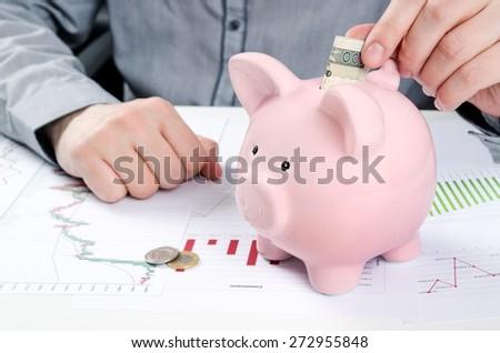 Man putting polish bill in piggy bank. Saving money concept - stock photo
