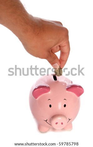 Man putting pound coin in piggy bank studio cutout