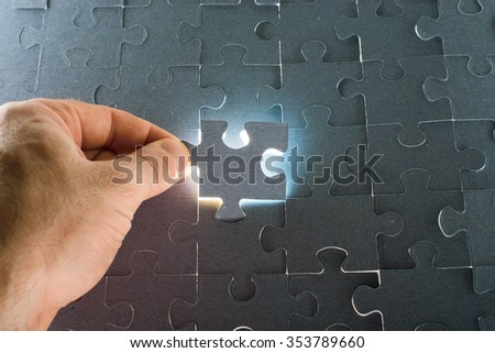 Man putting puzzle piece, close up view