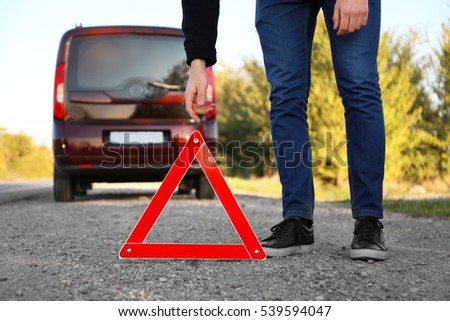 Man putting warning triangle on asphalt road. Emergency stop concept