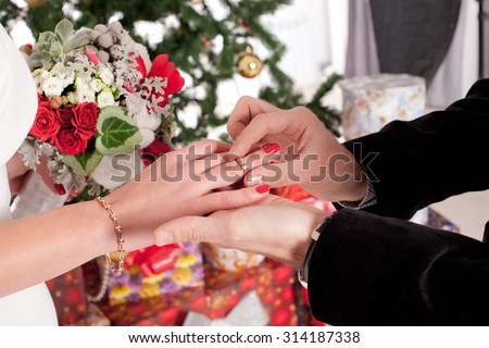 man putting wedding ring on woman hand. Christmas and New Year decoration - tree, gifts and wedding bouquet - stock photo