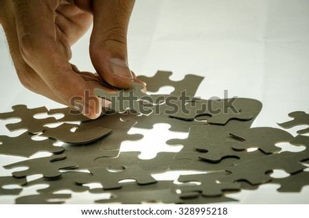 Man puzzle fits on a light surface - stock photo